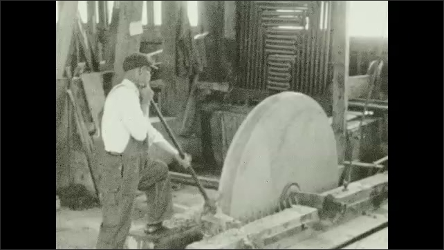 1930s: Two workers hammer on the edge of a stone. Worker holds a tool on the edge of a big circular stone that rotates with a mechanism. Tool smoothes the stone's edge while it rotates.