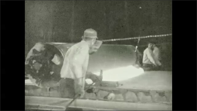 1930s: Crane unloads molten mixture into a machine where two men operate a big cylinder that stretches it and becomes glass. Mechanical blade cuts the glass at the end of the cylinder.