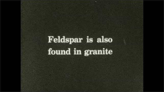 1930s: Machine rotates while it operates. Intertitle ????eldspar is also found in granite???? Pieces of stone lay around a stone with label ????eldspar???? Intertitle ????lay is weathered feldspar????