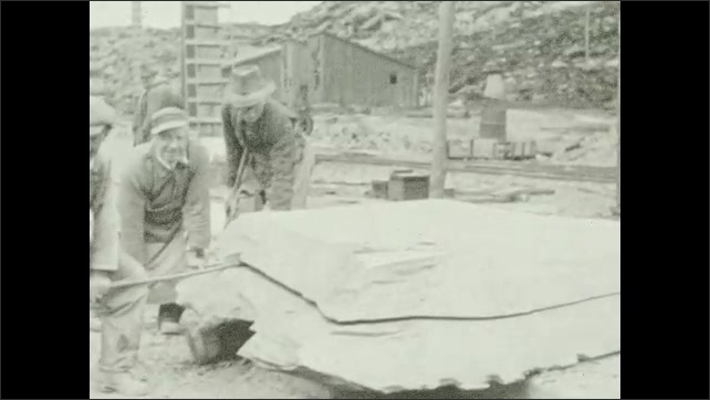 1930s: Workers break a piece of rock from the ground. They chain the rock into a crane. Workers break rock into two pieces. Worker breaks slate rock into several layers.
