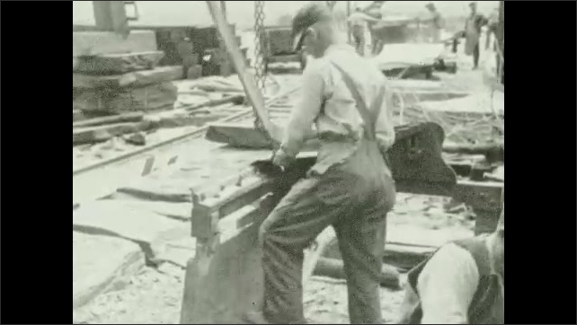 1930s: Worker breaks slate rock into several layers. Worker cuts a piece of slate into a square on a mechanical blade. Stacks of slate. Intertitle ????ricks are made by burning clay????