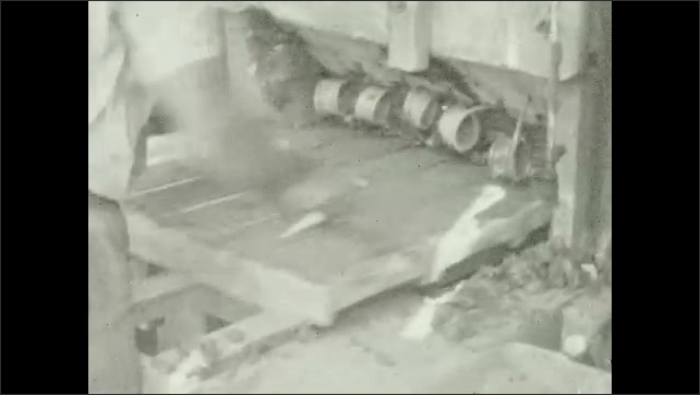 1930s: Clay mixture moves into a machine. Machine makes bricks, hands take the bricks from the machine. Man lays bricks on the ground to dry. Man moves rows of bricks that dry on the ground.