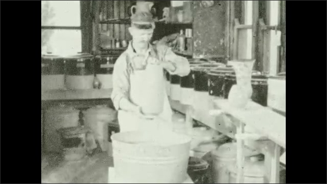 1930s: Man washes a clay pot on a container, several items lay on a table. Men carry clay pottery on their heads inside a warehouse.