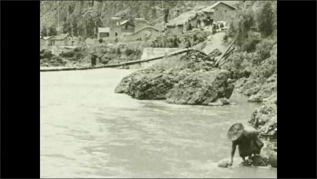1930s: UNITED STATES: man in traditional hat and costume. Lady gathers water from river. Lady with jug.