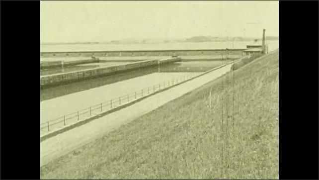 1930s: Pan across reservoir. Tilt up churning water. Pan across coastline.