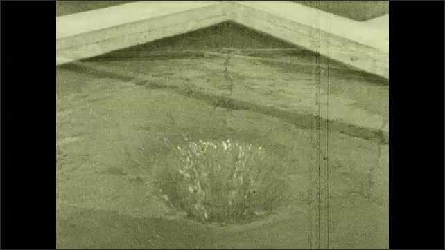 1930s: Intertitle. Pan across reservoirs. Water draining in tank.
