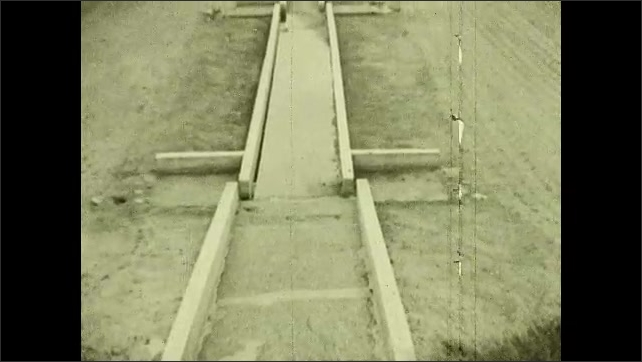 1930s: Pan across bed of sand. Tilt up wooden tracks in sand. Water flows through tracks.
