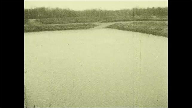 1930s: Tilt up water flowing into reservoir, pan across reservoir.