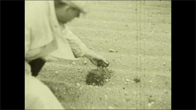 1930s: Animation of water filtering through sand. Man picks up handful of sand. Man pours sand into beaker. Hand stirs beaker.