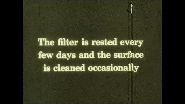 1930s: Magnifed view of organisms. Intertitle. Man looks at pieces of dirt. Close up, hand holds piece of water filter.