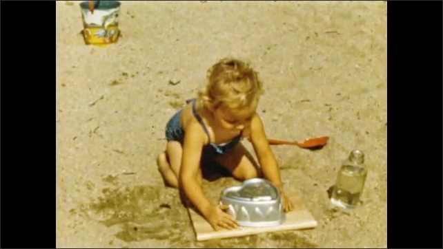 1950s: Children play on the beach.  Girl makes sand heart with mold.  Boy uses bucket.