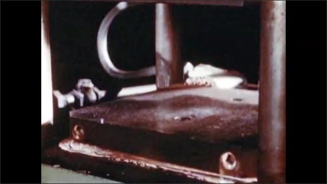 1950s: Men work in factory.  Man uses machine to take mold apart.