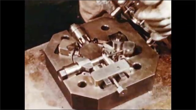 1950s: UNITED STATES: fingers place component in metal mould. Steel mould pieces. Hands put mould sections together. Powder poured into mould