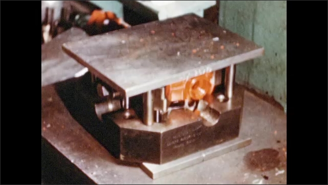 1950s: UNITED STATES: Hands put mould into furnace. Curing process of plastic mould. Hands remove steel from metal mould