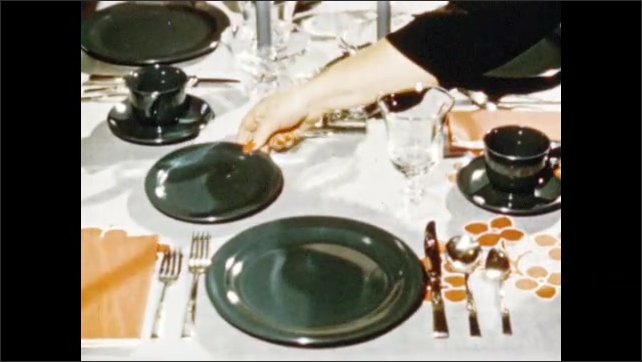 1950s: UNITED STATES: operator removes plastic ware from press. Dinner ware on table.
