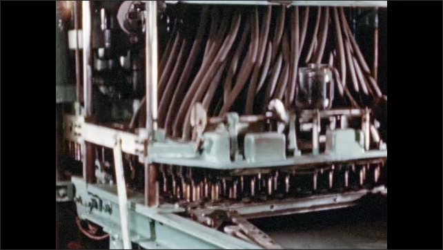 1950s: UNITED STATES: automatic machines in factory. Laid loads drum in factory. Cavities inside machine. Pellets pressed in machine. Feeder tubes release powder into buckets.