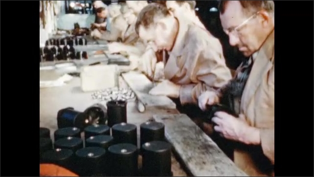 1950s: UNITED STATES: hands feel plastic mouldings during inspection. Flash removal with file. Men file plastic