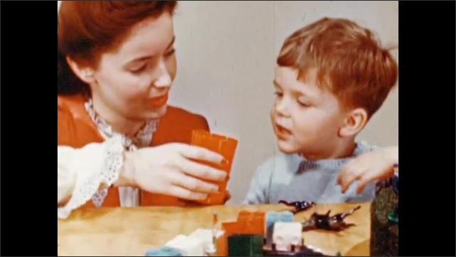 1950s: UNITED STATES: boys plays with plastic toys. Plastic figures on turntable. Boy drinks from plastic cup. Lady gives drink to boy