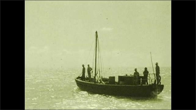 1930s: Men on boat in water. Men lift sail on boat.