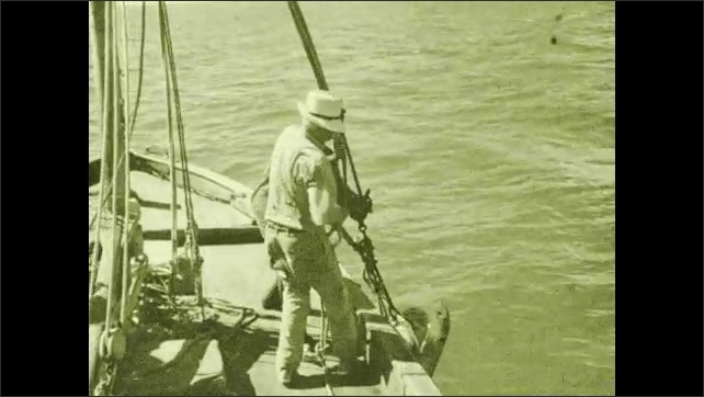 1930s: Shark twists and flails in the water. Men pull shark out of water.