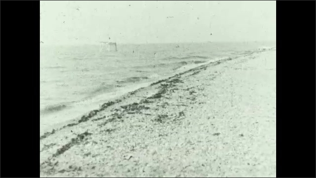 1930s: UNITED STATES: seaweed along tide line. View along stretch of beach