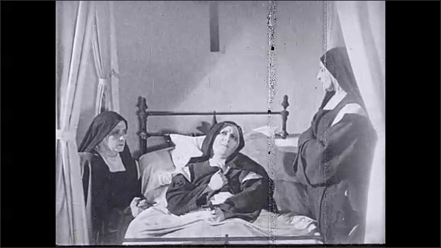 1930s: UNITED STATES: nuns sit by bed of sick lady. Lady unwell in bed. Nun grabs chest. Nun holds crucifix