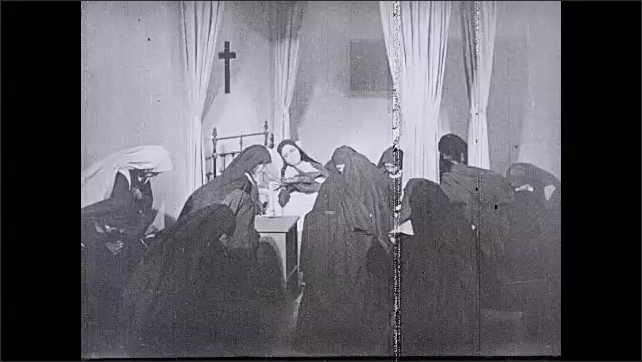 1930s: UNITED STATES: nuns pray around lady in bed. Death of nun. Lady cries with pearls in hand. Family in grief
