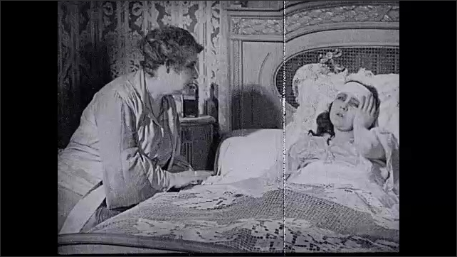 1930s: UNITED STATES: lady sick in bed. Lady sits by bed of patient. Statue of Mary.