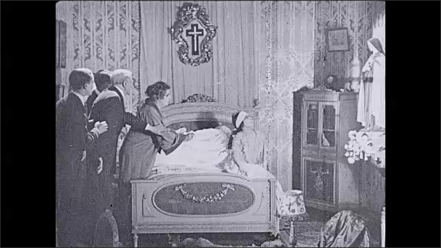 1930s: UNITED STATES: patient lies in bed. Lady hallucinates. Girl in bed talks to statue on wall. Family gather around lady in bed