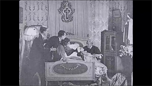 1930s: UNITED STATES: family gather around lady in bed. Clouds in sky. Lady prays to statue. Lady collapses in bedroom. Man catches lady. Girl sits in bed with parents
