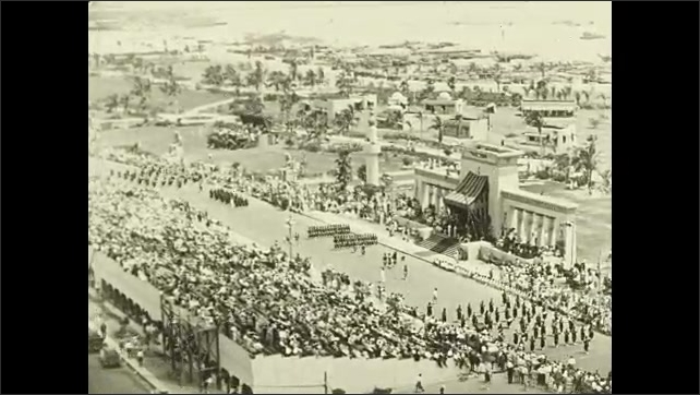 """1920s: Intertitle """"Passing in review"""". View of parade from up high."""