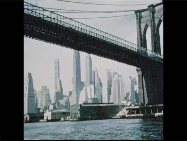 1950s: Manhattan skyline under Brooklyn bridge. Two women and a man stand on deck of boat, look out over water to city.