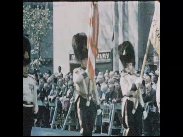 1950s: Marching band marches down street, high school drill team performs in parade.