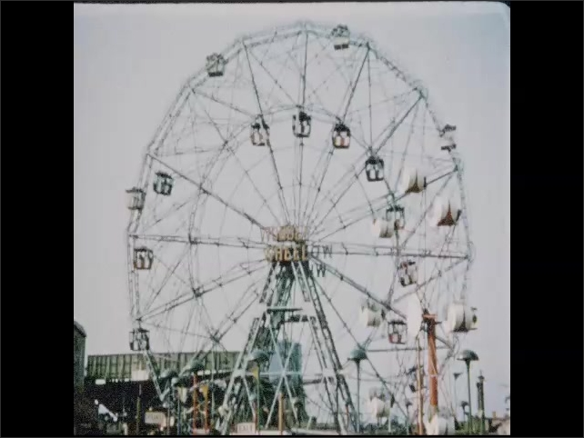 1950s: Man and woman sit in seat of parachute drop ride, smile, laugh. Large ferris wheel spins around. Cyclone roller coaster.