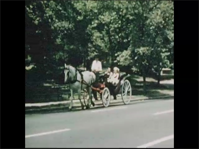 1950s: Man and woman ride in horse drawn carriage through Central Park. Man points to landmarks in park. Fountain and pond. Kids play baseball in baseball field.