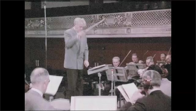 1950s: UNITED STATES: orchestra performs on stage. Conductor waves baton at orchestra. Musicians play violins.