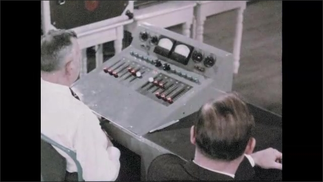 1950s: UNITED STATES: orchestra performs on stage. Sound engineers record music. Recording console in studio. Men lift up violins.
