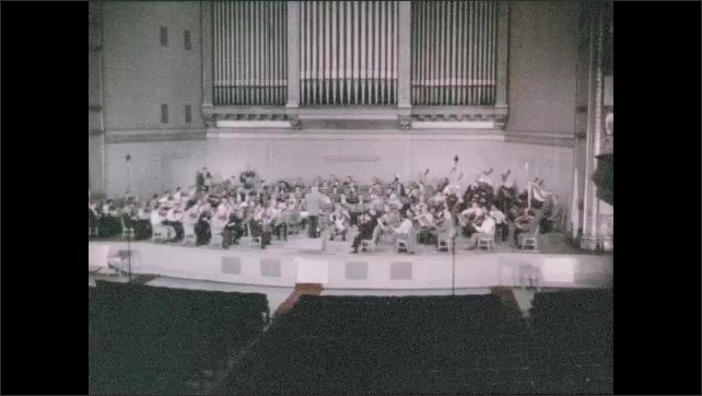1950s: UNITED STATES: engineer in sound studio. Stereophonic recording of orchestra on stage. Stereophonic playback.