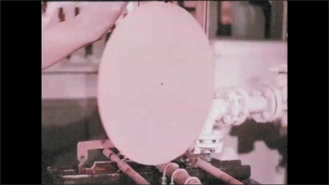 1950s: UNITED STATES: hand takes record from dip. Man inspects copper cover on record. Man works plating machine