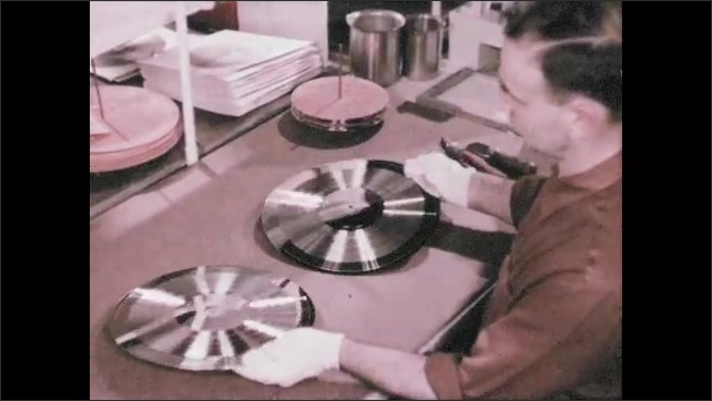 1950s: UNITED STATES: man splits lacquer and master from each other. Metal master and mold.