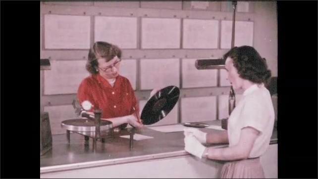 1950s: UNITED STATES: record in machine. Long play copy if record. First pressing of record. Lady inspects record. Lady listens to record during playback test.