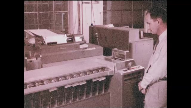 1950s: UNITED STATES: man watches record machine. Hands lay out cards