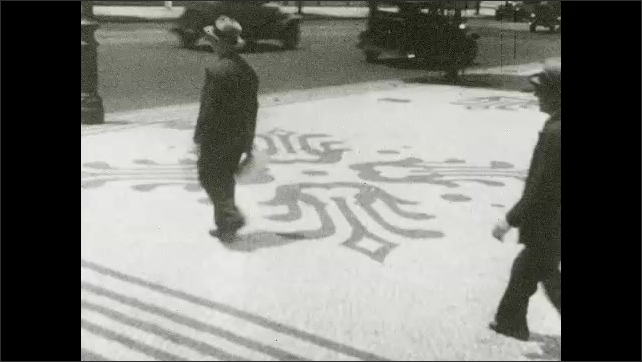 1930s: SOUTH AMERICA: mosaic floor in city. Men walk along patterned floor on sidewalk. Pedestrians in city.