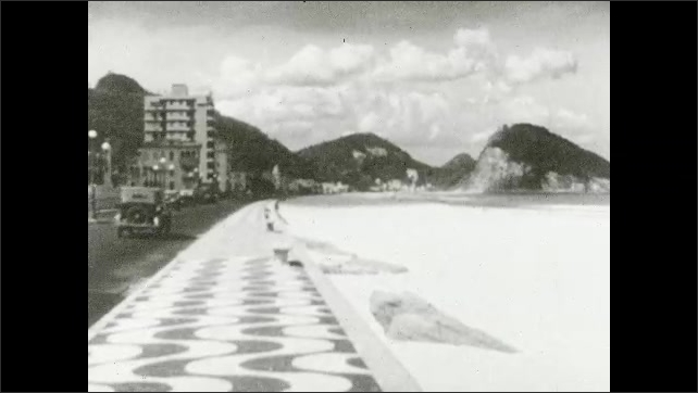 1930s: SOUTH AMERICA: view along street by ocean. Decorated sidewalk along coast.