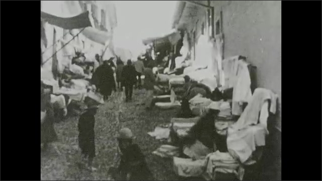 """1930s:??Women walk through busy market full of vendors. Woman weaving a blanket on a hand-held loom. Intertitle """"the snowy Cordillera range in the Andes"""".??"""