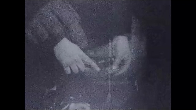 1930s: Close up, hands connect machine parts. Hands screw machine parts together.