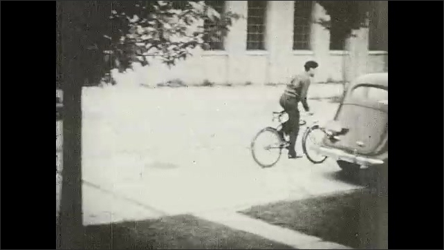 1930s: UNITED STATES: boy rides bike outside building. Boy cycles home. Boy cycles along pavement. Boy cycles across road.