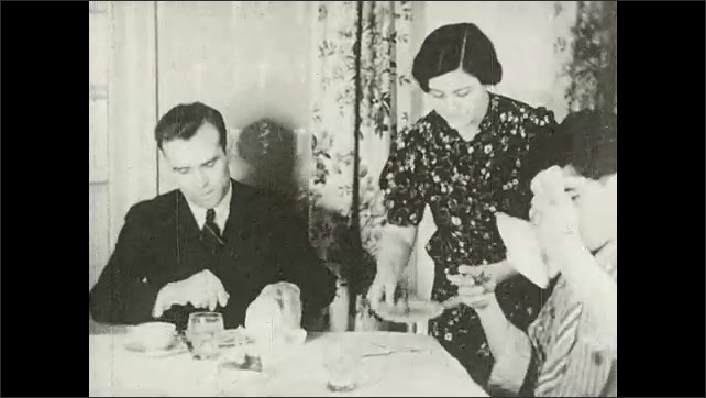 1930s: UNITED STATES: family eat together at table. Boy drinks from glass. Lady talks to boy