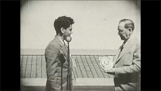1930s: UNITED STATES: Boy presents to crowd. Boy receives award at event. Man gives shield to boy. Audience clap.