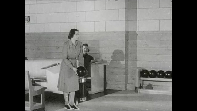 1930s: Woman stands, holds bowling ball, launches ball down lanes, knock down all pins.